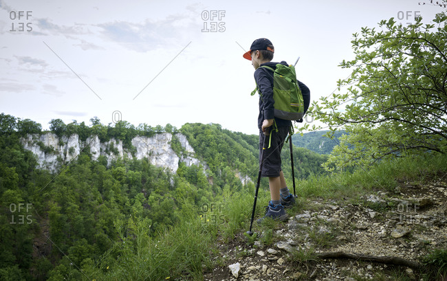 Boy standing with hiking poles at the edge of plateau while looking at landscape at Swabian Jura