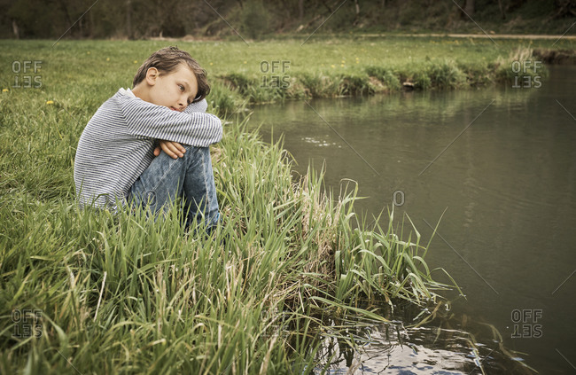 Side view of lonely boy sitting at riverbank while thinking in forest