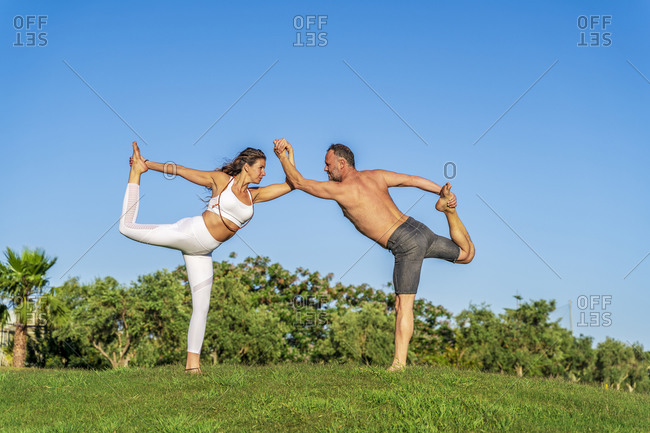 Mature couple doing yoga on lawn in sunshine together