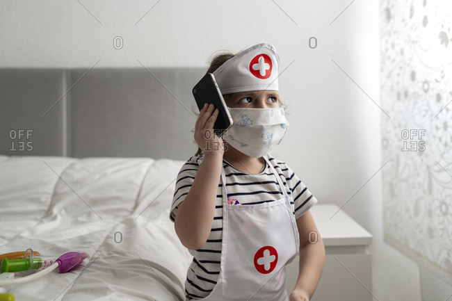 Girl in a doctor's costume wearing a mask and calling