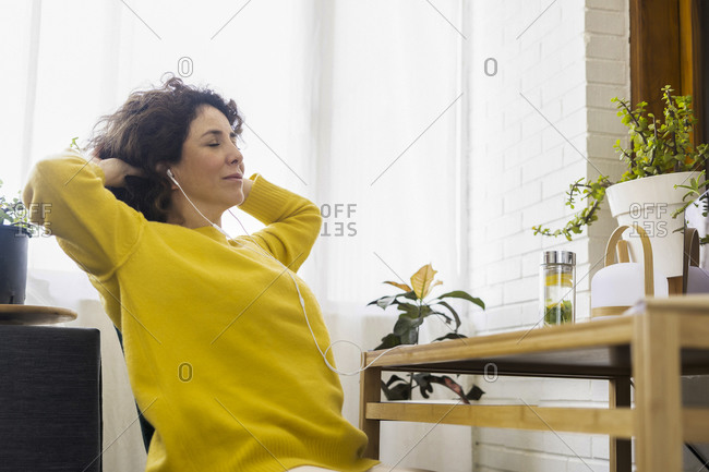 Woman having a break from working at desk in home office
