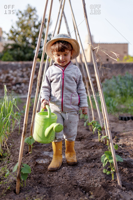 Smiling cute girl holding watering can standing under trellis at orchard