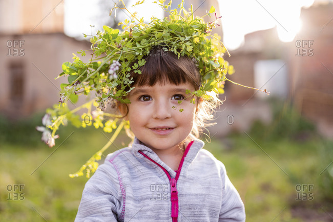 Close-up of smiling cute preschool girl wearing plant crown while standing at orchard