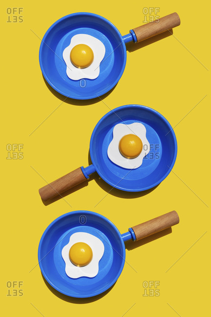 Illustration of fried eggs on blue pans against yellow background