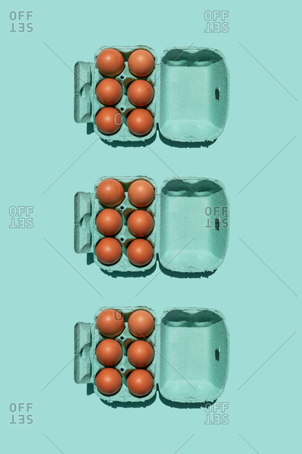 Studio shot of chicken eggs in turquoise colored cartons