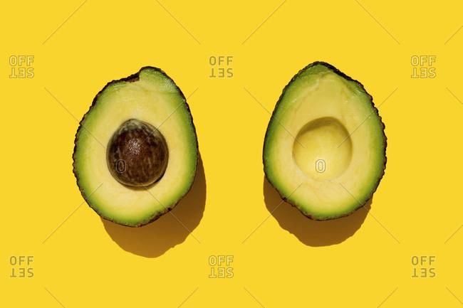 Studio shot of halved avocado on yellow background