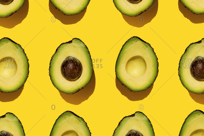 Pattern of halved avocados on yellow background