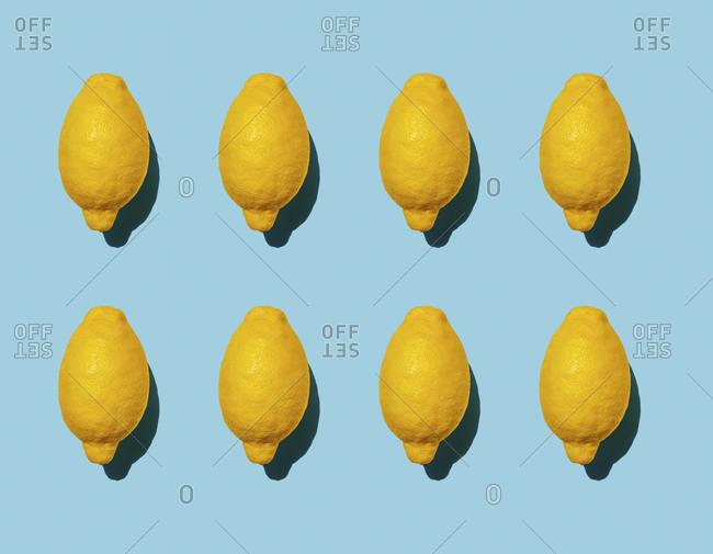 Pattern of ripe lemons against blue background