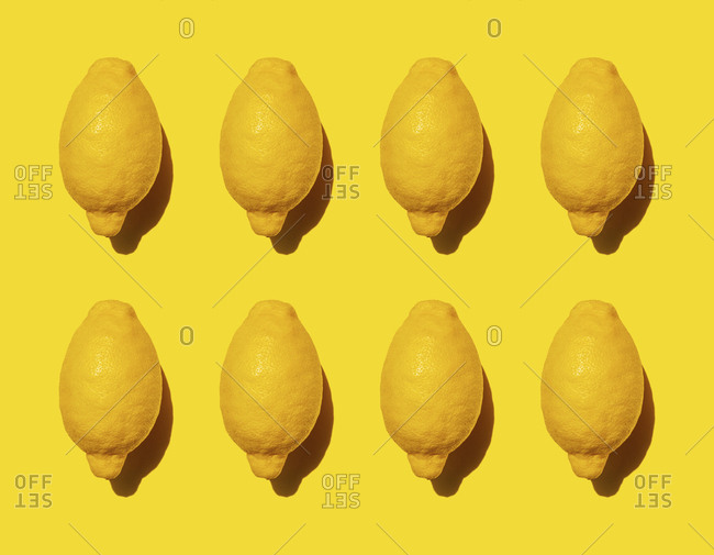 Pattern of ripe lemons against yellow background