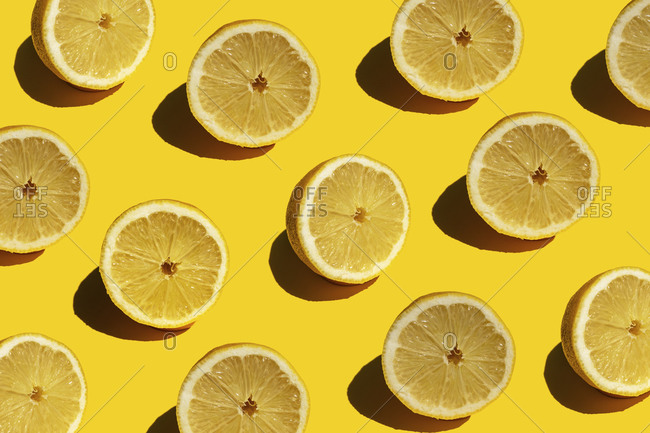Seamless pattern of fresh halved lemons against yellow background