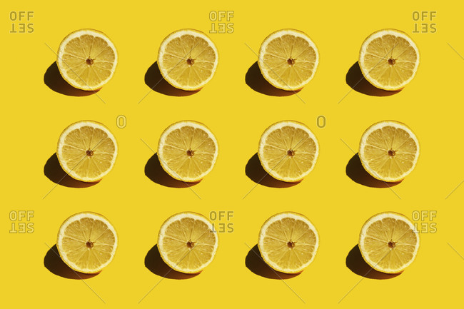 Pattern of fresh halved lemons against yellow background