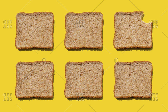 Studio shot of six slices of wheat bread against yellow background