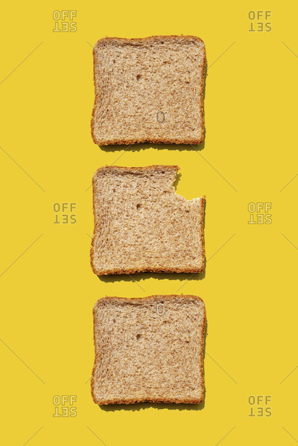 Studio shot of three slices of wheat bread against yellow background