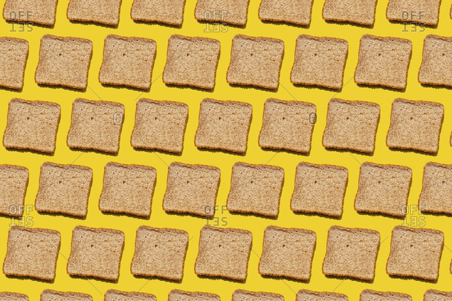 Pattern of slices of wheat bread against yellow background