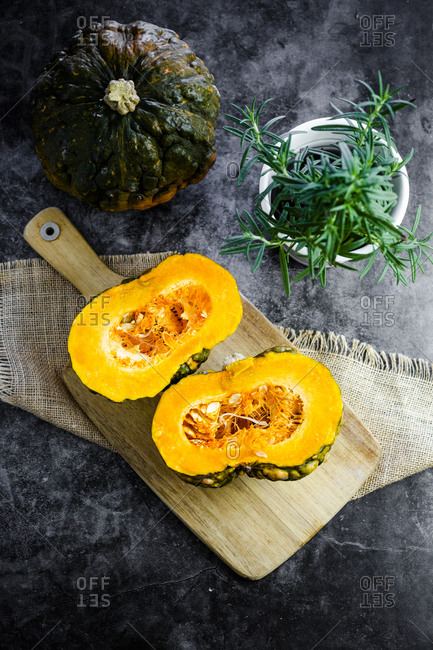 Halved pumpkin on wooden cutting board and rosemary