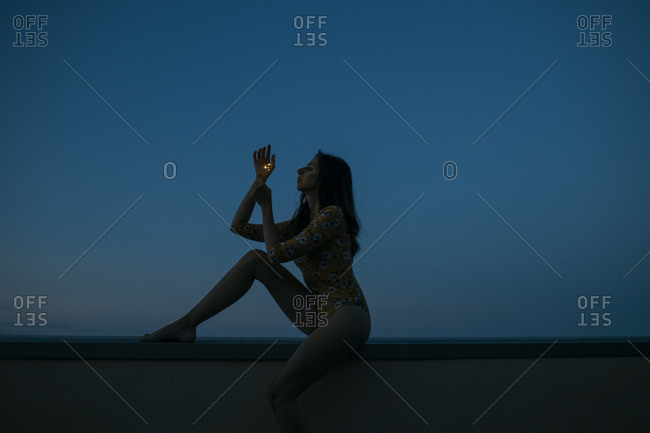 Side view of woman holding sparkler while sitting on retaining wall against clear blue sky during sunset