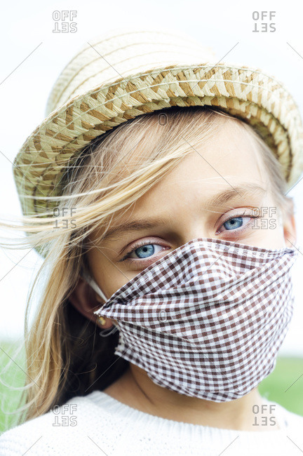 Close-up portrait of girl wearing face mask and hat