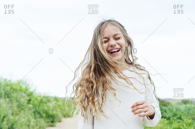 Carefree blond girl standing with eyes closed against sky