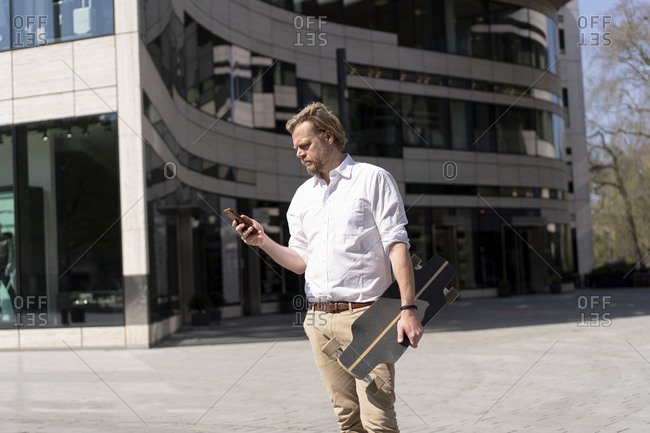 Businessman holding skateboard and checking smartphone in the city