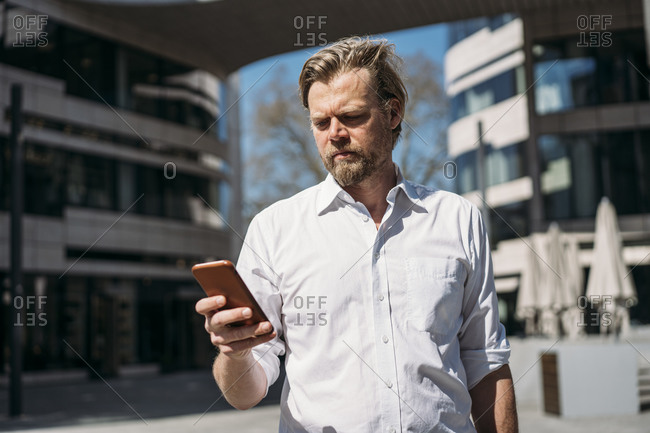 Businessman checking smartphone in the city