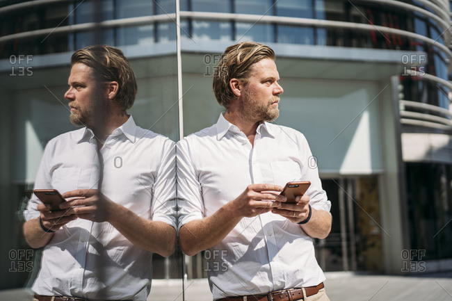 Businessman in the city leaning against glass front holding smartphone