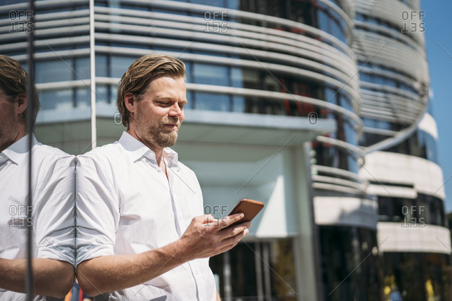 Businessman in the city leaning against glass front checking smartphone