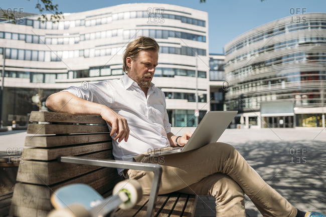 Businessman sitting on a bench in the city using laptop