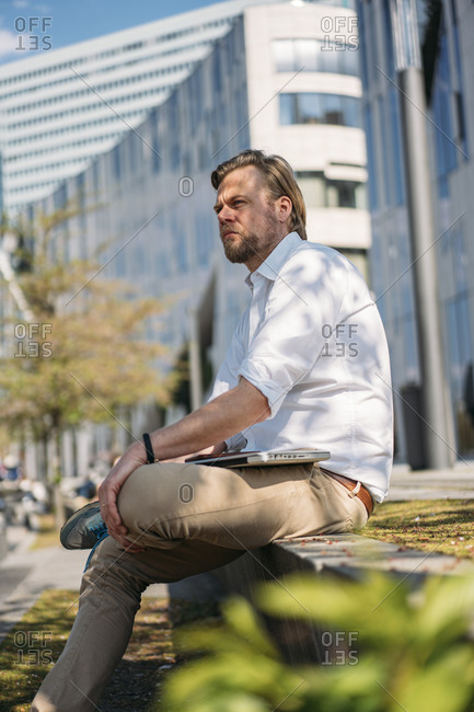 Businessman having a break in the city sitting on a wall