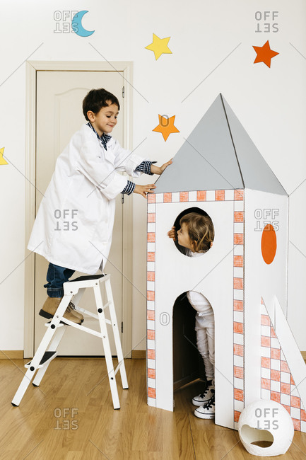 Siblings playing astronaut and researcher at rocket