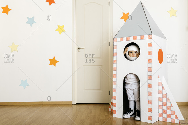 Girl wearing costume and playing astronaut in rocket