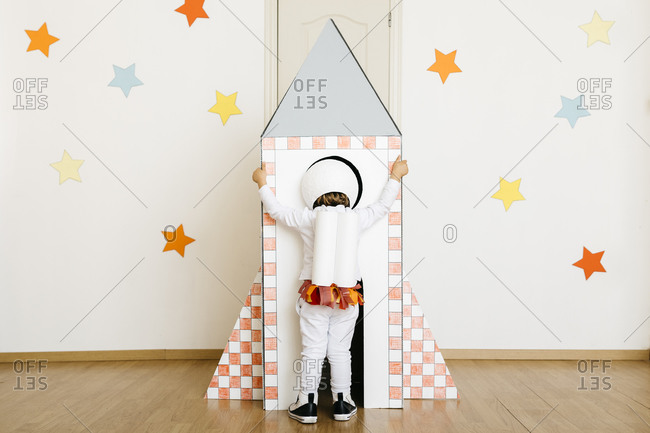 Girl wearing costume and playing astronaut looking into rocket