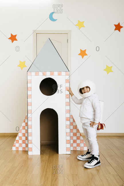 Girl wearing costume and playing astronaut at rocket