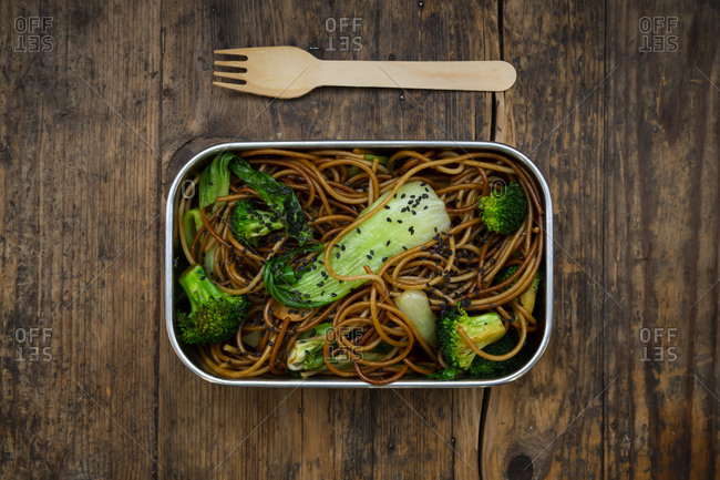 Lunch box of soba noodles with bok choy- broccoli- soy sauce and black sesame seeds