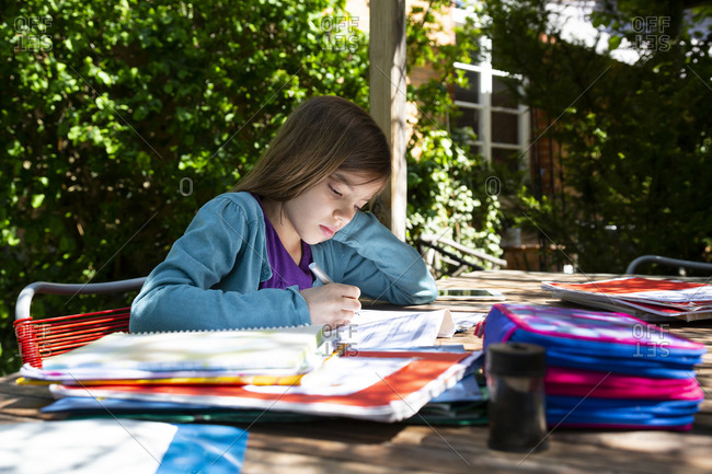 Girl sitting at garden table doing homework