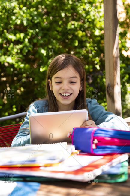 Girl sitting at garden table doing homework and using tablet