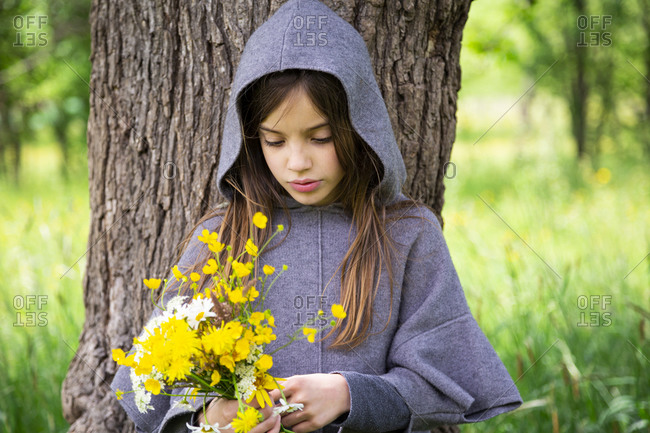 Girl picking yellow wildflowers outside