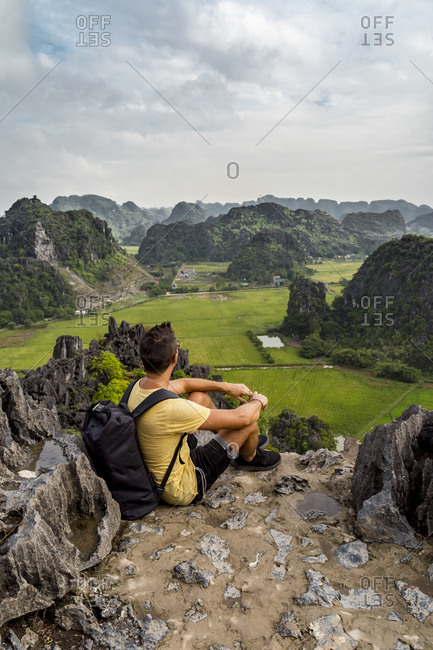 Vietnam- Ninh Binh Province- Ninh Binh- Male hiker admiring scenic landscape of Hong River Delta from top of karst formation