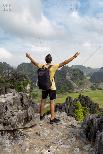 Vietnam- Ninh Binh Province- Ninh Binh- Male hiker standing with raised arms at edge of Hong River Delta karst formation
