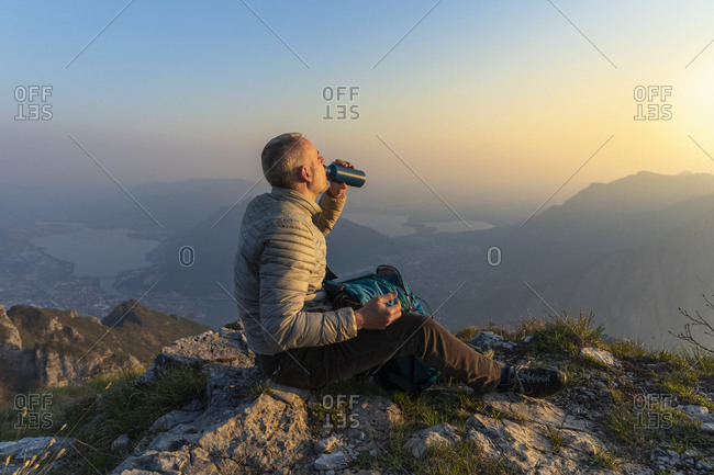 Hiker drinking on viewpoint at sunset- Orobie Alps- Lecco- Italy