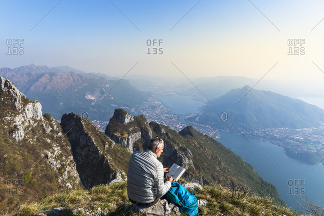 Rear view of hiker reading a book on mountaintop- Orobie Alps- Lecco- Italy