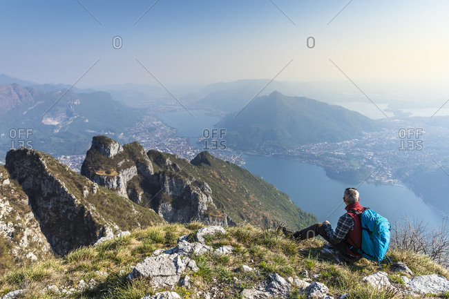 Rear view of hiker sitting on mountaintop- Orobie Alps- Lecco- Italy