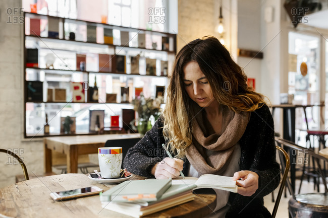 Woman writing in notebook in coffee shop
