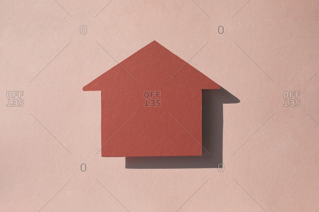 Studio shot of house shaped paper cut against pastel pink background