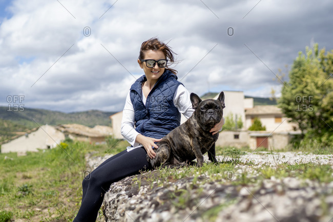 Portrait of woman and her bulldog sitting outdoors- Castilla La Mancha- Spain