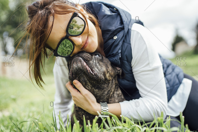 Portrait of happy woman cuddling her bulldog on a meadow