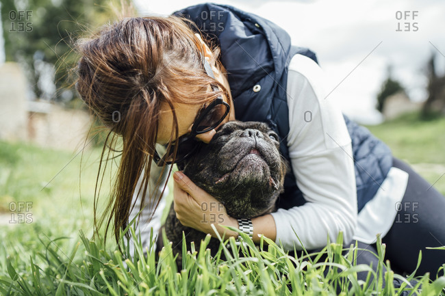 Woman cuddling her bulldog on a meadow