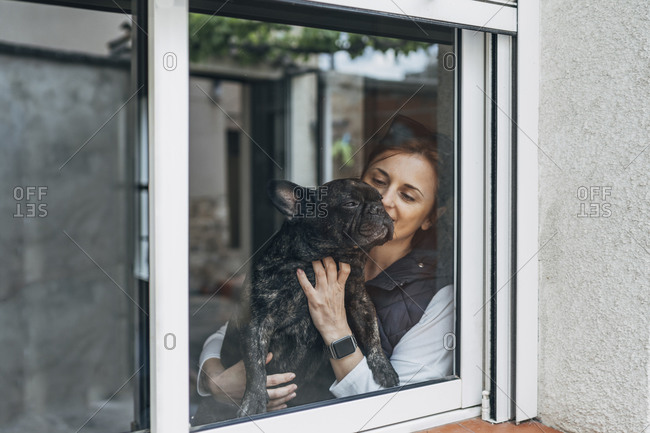 Woman cuddling her bulldog behind window