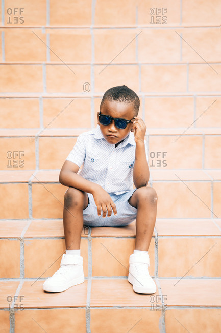 Portrait of cool little boy wearing sunglasses sitting on stairs outdoors