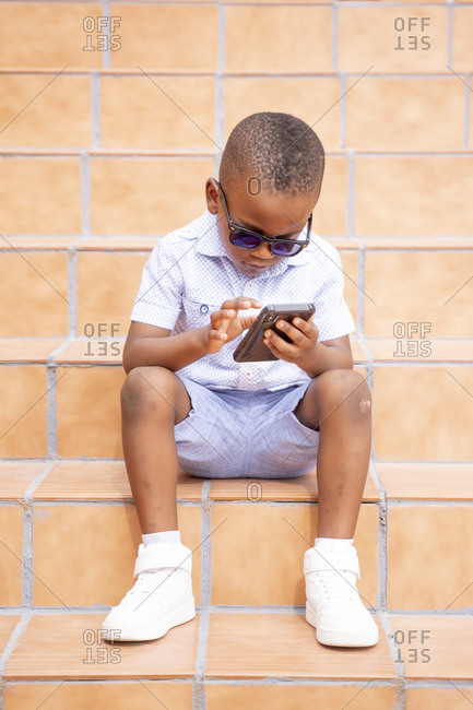 Portrait of cool little boy wearing sunglasses sitting on stairs outdoors using cell phone