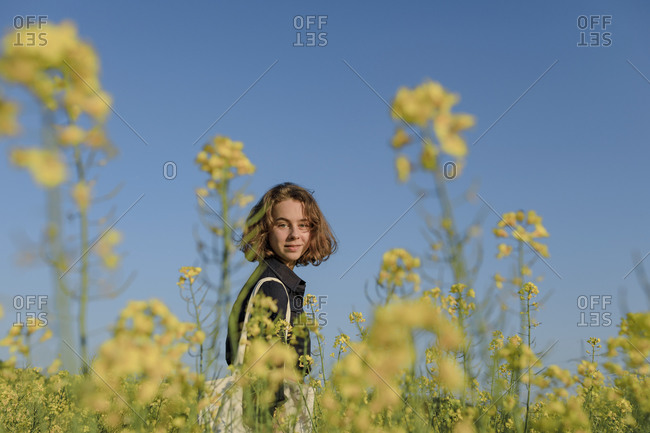 Portrait of smiling teenage girl standing in rape field